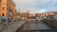 The Miljacka River in Sarajevo, National Library where our heroes try to crash a presidential reception on the left.